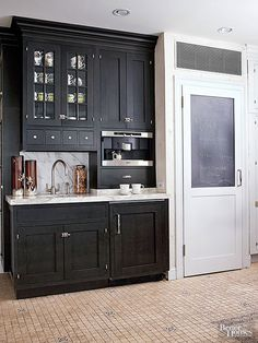 A section of walnut-stained cabinets serves as a beverage center complete with a bar sink, built-in espresso maker, coffee grinder, and a refrigerator drawer for cream and other extras.