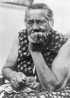 An elderly  [Roma/Sinti] woman, a survivor of Auschwitz, with a tattooed forearm.