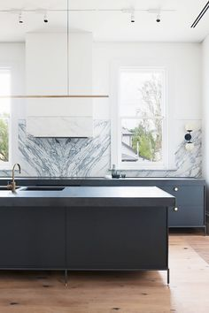 Stunning kitchen with gray cabinents, marble backsplash, and a gold pendant light