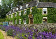 The Swan Hotel, ivy-clad hotel situated in Bibury, UK, overlooking the River Coln.
