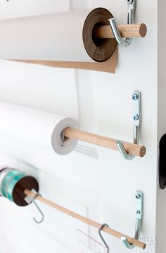Great idea for organizing wrapping papers + spools of ribbon: Hooks + dowels.
