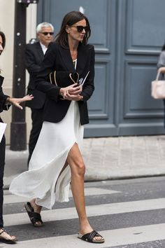 Long white slip dress with a black blazer and black slides. Chic summer look!