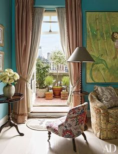 A sitting area at fashion designer Lorry Newhouse's New York City home features turquoise walls and a slipper chair upholstered in a Braquenié fabric.