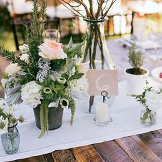 """Tables were decorated with vintage glassware, as well as vases of pussy willow and herbs like rosemary, basil, and thyme. """"We wanted lots of little vases instead of one big arrangement,"""""""