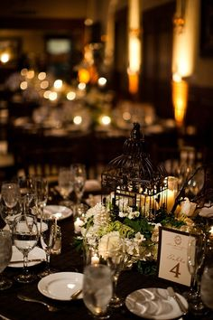 Reception table setting details - Black tablecloth, white candles, black birdcage with white and green floral arrangement as centerpiece, and elegant black framed table number with gold font - wedding photo by Michael Norwood Photography