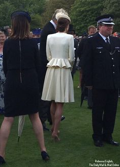 This offers another look at the back of Kate's outfit; I believe we also see Rebecca Deacon, Kate's private secretary, in the navy blue on the left.