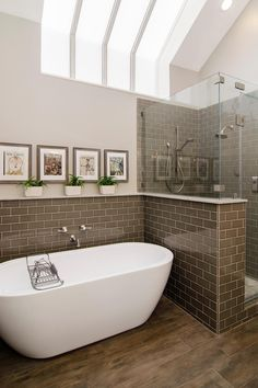 This airy bathroom blend traditional details with fresh modern twists. Narrow strips of skylight let the natural light pour in on the crisp gray tile and hardwood floor.