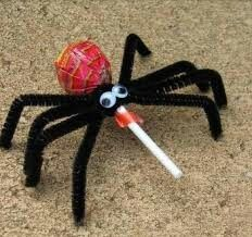 Halloween spider decoration using black pipe cleaners for the legs and a red lollipop for the body with glued on Eyes