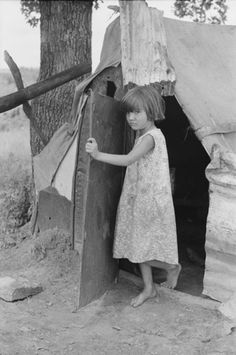 1939  Child of agricultural day laborer coming out of tent near Spiro. Sequoyah County, Oklahoma, Photo by Russell Lee, Farm Security Administration.