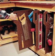 Using re-tractable peg board to store tools under a workbench.