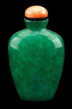 Chinese jadeite snuff bottle     Tall shouldered tapering to a flat oval base, coral stopper, stone of beautiful deep green hue.     H: 2 3/4 in.