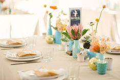 centerpiece inspiration: pinks & oranges in blue/green vessels, neutral linens, hints of gold