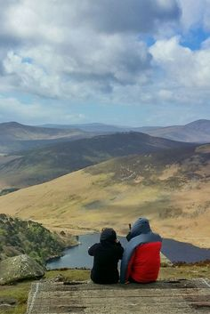 Hikers overlooking Guinness Lake in Ireland, while hiking in the Wicklow Mountains on Ireland's famed Wicklow Way, one of the most spectacular long distance hiking routes in Ireland.