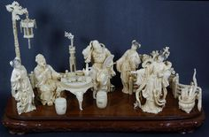 """CHINESE CARVED IVORY PARLOR SCENE GROUP Chinese hand carved ivory group figure. Depicts a parlor scene with 3 maidens. An old man is sitting at a table and there is a man helping him. Also in the scene is garden seats, lamp post and lantern, torch, flower pot and pedestal and boiling pot with scrolls, scepter and feather fan. Has wooden base. Measures 11"""" height x 21"""" length +2 1/4"""" base height"""