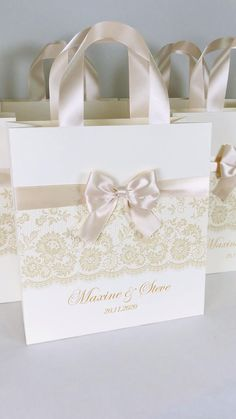 Elegant ivory wedding welcome bags with Champagne satin ribbon handles, bow and gold names. Chic personalized wedding gifts and favors for guests. #welcomebox #personalizedgifts #giftbags #weddingfavor #weddingwelcomebags #welcomebags #weddingfavorideas #weddingparty #weddingfavorideas #weddingparty #weddingfavour #weddingwelcome #ivorywedding #elegantwedding #champagnewedding #goldwedding #weddingbag