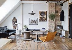 Stue med murstensvæg og møbler i dæmpede farver