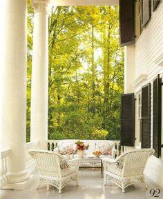 White Greek Revival porch with black shutters, large columns, wicker - Architectural renovation by Allan Greenberg; interior design by Amelia Handegan in Hot Springs, Virginia - Veranda