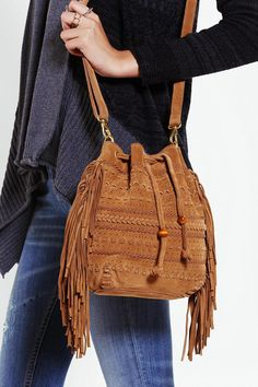 Soft suede bucket bag with fringe trim. #urbanoutfitters
