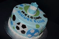 - Blue, green & brown baby shower cake with soccer balls and baby gumpaste tennis shoe