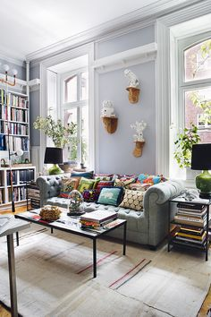 A calm blue bachelor pad living room in the heart of the city with bohemian accents.