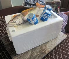 Groom's Cakes - The ice chest is red velvet cake on the top half, the bottom half is a cake dummy. The fish is RKT covered with fondant and hand-painted. The beer cans are RKT covered with fondant. The labels are sugar sheets and the lids are molded fondant. The ice is rock candy.