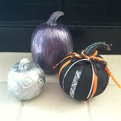 DIY decorated pumpkins using acrylic paint, glitter, and ribbon. Silver pumpkin uses glow in the dark t-shirt puffy paint.