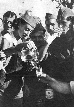 """Una miliciana sirviendo el agua a sus compañeros. """"Estampa"""" 29 de Agosto 1936."""