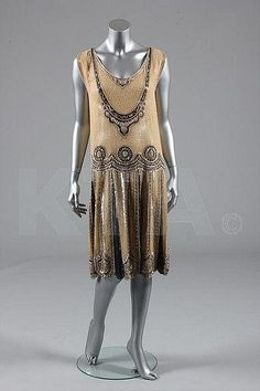 Description: A beaded and sequined flapper dress, circa 1928, the pale apricot muslin ground spangled overall with clear glass seed beads, with black, gold and pearlescent beads and sequins. Front