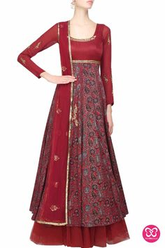 Joy Mitra maroon azrak anarkali with a net underlayer and a cloth tassel tie up at the back. It has golden sequins and thread work embroidery on the neckline and an embellished band around the yoke. It comes along with a matching maroon net dupatta with gloden floral sequins flower motifs
