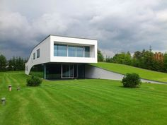 Stunning green-roofed Autofamily House features a drive-thru a...
