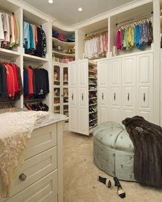 A traditional walk in closet is an elegant place for the lady of the home to keep her clothes. Large slide-out drawers provide secret storage that's functional and looks good.