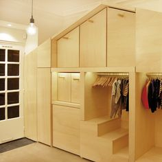 A shelving unit displaying Children's clothes doubles as a plywood playhouse with a sliding staircase, swinging doors and removable furniture. This is some serious carpentry! Children would love it! Heck, I'd love it!