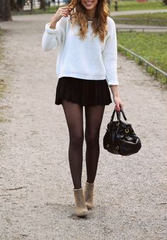 Cute fall outfit. White sweater paired with a black pleated mini-skirt over tights and tan ankle boots.