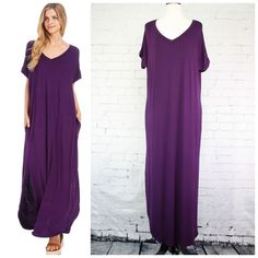 Loose fitting deep purple v-neck maxi with short sleeves and side pockets. Soft, comfortable jersey fabric. Hems are rounded in front and back, and there is a drop pleat on upper back.