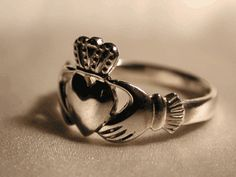 The Irish claddagh ring. The symbols are said to correspond to the qualities of love (heart), friendship (hands), and loyalty (crown). Meant as a friendship ring, promise ring, engagement ring, or wedding ring depending on which finger and hand you wear it on.