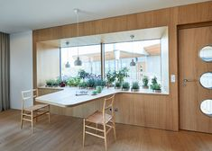 This window has a wide sill with lots of plants, that also extends and becomes a table for two.