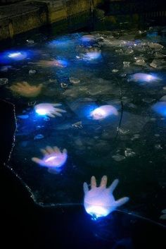 20 Cool Glow Stick Ideas ~ like this Glow Stick Floating Hands! Creepy! Fill surgical gloves with glow sticks, blow them up, and let them float in your pool or align them up your walkway to the door...hehehehe!