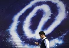 "A Chinese man checking on his smartphone walks past an ""at"" sign on display on a street in Beijing, China Thursday, Sept. 4, 2014. The editor-in-chief and several employees of an influential Chinese financial news site were taken away by police in an investigation over allegations that the executives and journalists had extorted money from companies by threatening to publish negative news about them, the official Xinhua News Agency said Thursday."