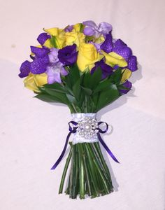 Yellow roses, purple Vanda orchids and purple freesia and lisianthus