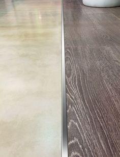 Terminación cuadrada de acero que une pisos de porcelanato y revestimiento de madera.