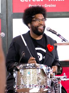 Questlove stops jamming for a smile during a performance with the Roots on June 25 in New York
