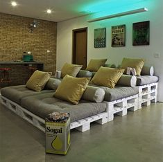 DIY Recycle Pallet Stadium-Style Seating: Reclaimed wood shipping pallets create a cozy spot for friends to gather in this home theater. The pallets also serve double-duty as storage for DVDs,magazines, and books.
