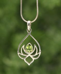Teardrop pendant of sterling silver depicts a budding lotus flower and is inlaid with a glittering peridot gemstone. Hangs from an 18 inch chain.