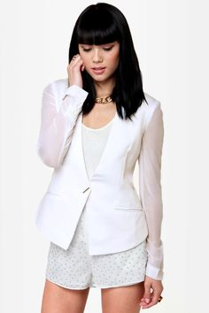 The Blazer of Glory White Blazer has a tailored feminine fit in thick white knit with sheer chiffon sleeves A slim silver button fastens the collarless silhouette with faux welted pockets on either side. Padded shoulders. Bodice is line.
