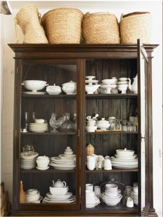 Wood cabinet contrasts with white casually stacked china and baskets.  Beautiful textures.
