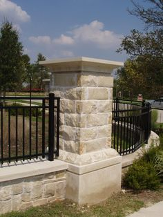 stone fence with brick or limestone columns and wrought iron gate with a lock on it for huge back yard