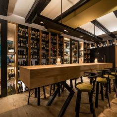 all interior finishings in oak, u-shaped benches, counter, wine room waxed in black steel including wine racks, niches