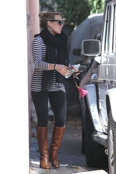 Brown boots with black leggings, black and white top.  Stripes and scarf.