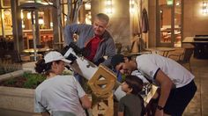 A man shares his telescope with the street and shows people Saturn