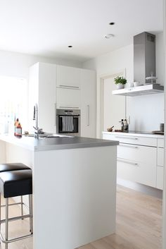 All white kitchen with exposed hood, painted cabinets, aluminium plinth, island with place for breakfast. love the island top Kitchen Inspirations, Interior, Home, Kitchen Remodel, New Kitchen, White Modern Kitchen, Kitchen Dining Room, Home Kitchens, Kitchen Style